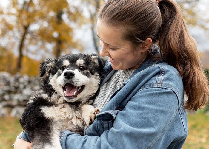 mujer-cogiendo-en-alto-a-su-perro-para-calmarlo-escuela-canina-la-tejera